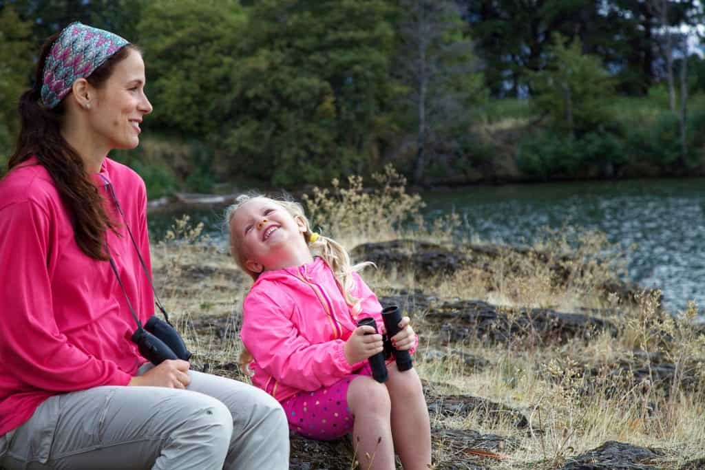 Mother and daughter smiling about pediatric dentistry by a lake